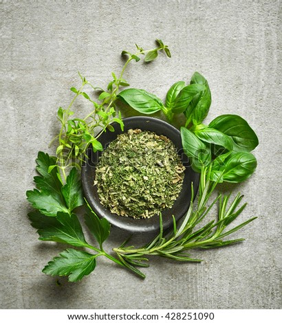bowl of dried herbs and fresh herbs on gray stone background, top view - stock photo