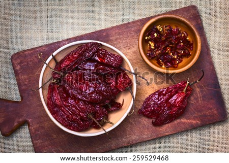 Bowl of dried (slightly hot) red aji chili pepper found in Bolivia and used for seasoning photographed with natural light (Selective Focus, Focus on the peppers on the top in the bowl) - stock photo
