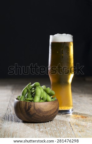 Bowl of edamame and a glass of beer sitting on a rustic wooden table. - stock photo