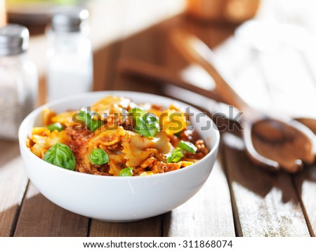 bowl of farfalle bowtie pasta with beef, basil leaves and tomato sauce - stock photo