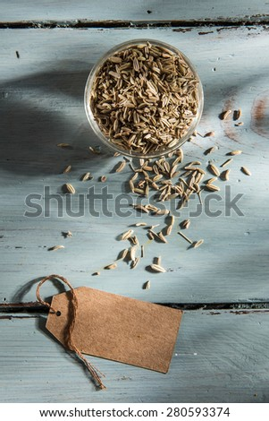 bowl of fennel seeds with a blank label, on a wooden background - stock photo