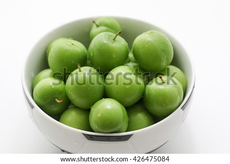 Bowl of fresh and green plums. - stock photo