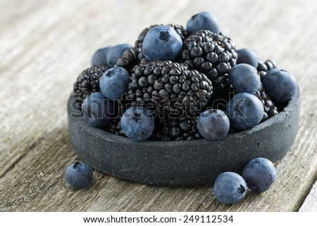 bowl of fresh blackberries and blueberries on a wooden background, close-up, horizontal - stock photo