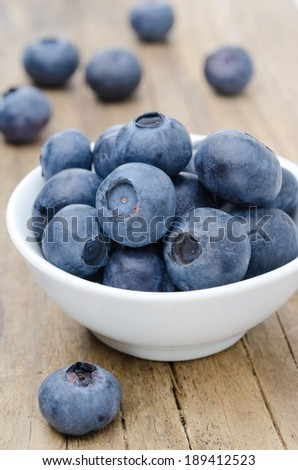 bowl of fresh blueberries on a wooden background