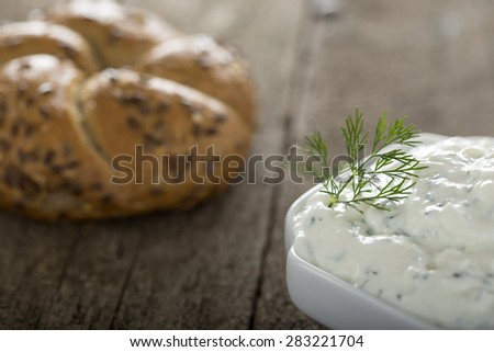 Bowl of fresh cheese sauce on wooden background with one bagel in background - stock photo