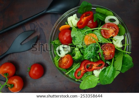 Bowl of fresh colorful salad with fork and spoon on wooden surface - stock photo