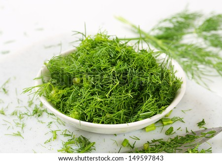 bowl of fresh cut dill with sharp knife