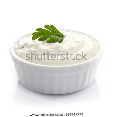 Bowl of fresh garlic dip sauce on white background - stock photo
