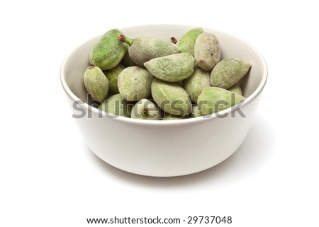bowl of fresh green almonds isolated on a white studio background.