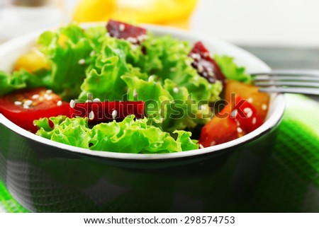 Bowl of fresh green salad on table with napkin, closeup