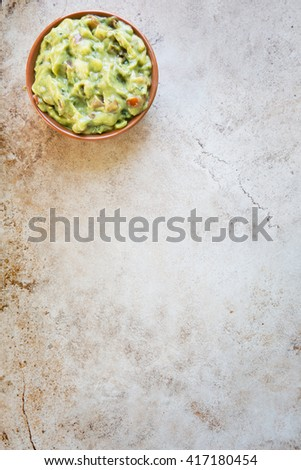 Bowl of fresh guacamole  n stone surface with copy space and viewed from above. - stock photo