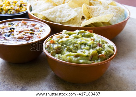 Bowl of fresh guacamole, with chips and salsa ready to eat.