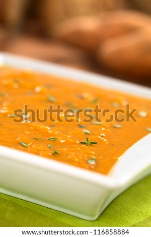 Bowl of fresh homemade sweet potato soup with thyme (Selective Focus, Focus one third into the soup) - stock photo