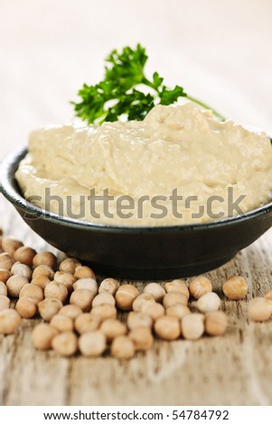 Bowl of fresh hummus with raw organic chickpeas - stock photo
