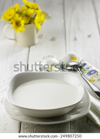 bowl of fresh milk waitng for cereal - stock photo