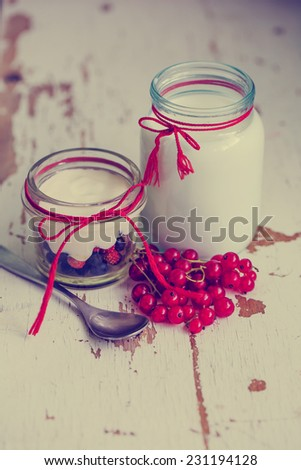 Bowl of fresh mixed berries and yogurt with farm fresh redcurrant served on a wooden table - stock photo