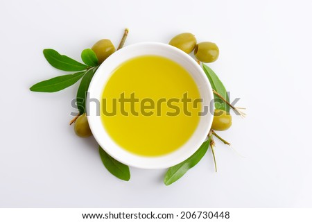 bowl of fresh olive oil and olive branches on white background - stock photo