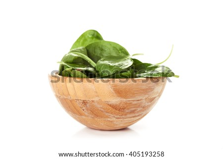 bowl of fresh raw green spinach isolated on white background/ healthy food