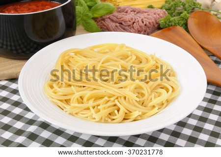 Bowl of fresh spaghetti, bolognese sauce ingredients in the background. - stock photo