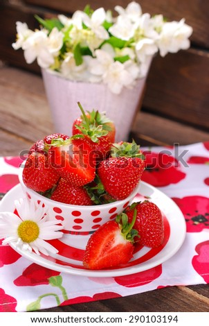 bowl of fresh strawberries and jasmine flowers in bucket on rustic wooden table
