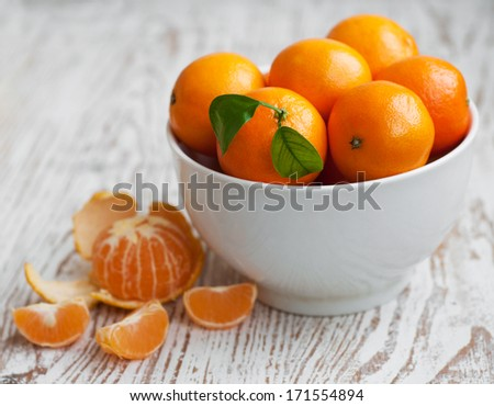 Bowl of fresh tangerines on a wooden background - stock photo