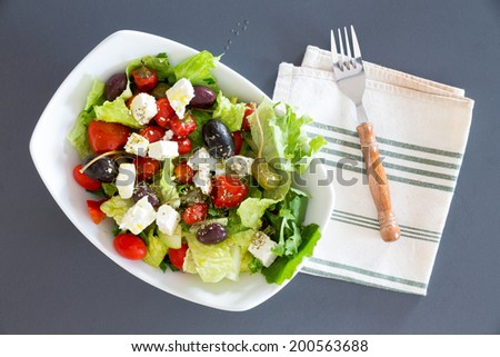 Bowl of freshly seasoned Mediterranean salad with assorted olives, lettuce, tomato and feta cheese ready to eat served on a blue table cloth with a napkin and fork, view from above - stock photo