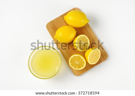 bowl of freshly squeezed lemon juice and ripe lemons on wooden cutting board - stock photo