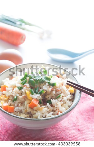 Bowl of fried rice, carrot and egg on pink fabric, spoon, chopsticks and ingredients for background - stock photo