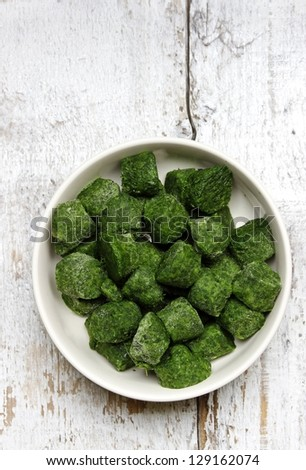 Bowl of frozen spinach isolated on white wooden background - stock photo
