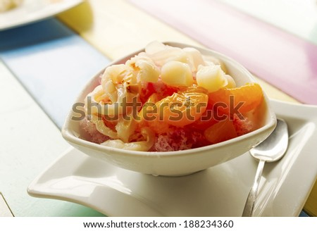 Bowl of fruits dessert with ice on colorful wooden table