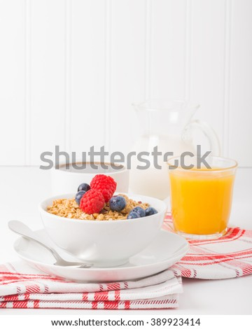 Bowl of granola and fresh berries with coffee and orange juice. - stock photo