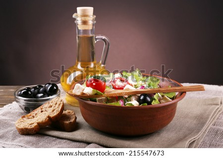 Bowl of Greek salad served with olive oil on sacking napkin on wooden table on dark background