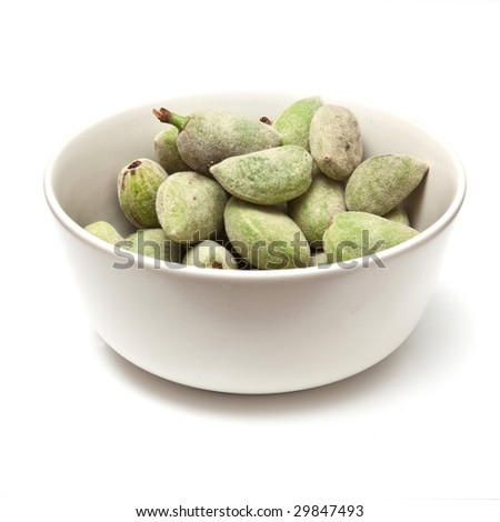 Bowl of green almonds isolated on a white studio background