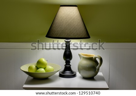 Bowl of green apples, lamp and pitcher on table.  Scene is illuminated only by soft light from lamp. - stock photo
