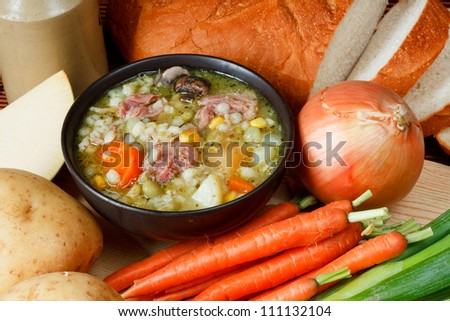 Bowl of ham broth in kitchen setting surrounded by ingredients, crusty bread and butter - stock photo