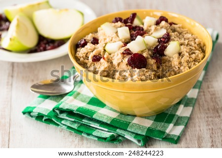 Bowl of healthy breakfast oatmeal with apples and cranberries on top
