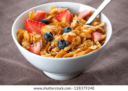 Bowl of healthy corn flakes breakfast cereal topped with fresh blackcurrants and strawberries served in a white ceramic bowl for a delicious meal - stock photo