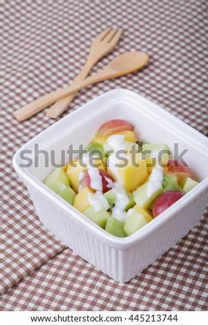 Bowl of healthy fresh fruit salad with yogurt - stock photo