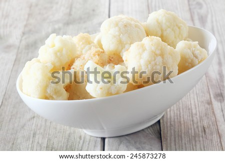 Bowl of healthy fresh steamed or microwaved white cauliflower broken into florets and served on a rustic grey wooden table, tilted angle close up view - stock photo