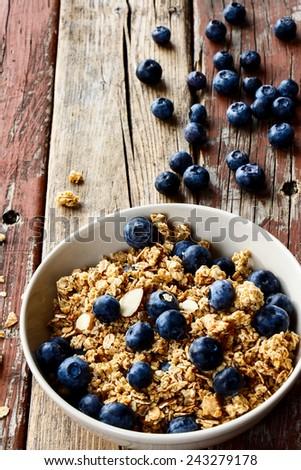 Bowl of healthy multi-grain granola with fresh blueberries over rustic wooden background. Selective focus. - stock photo