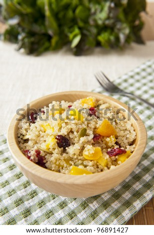 Bowl of healthy quinoa salad with dried fruit and pumpkin seeds - stock photo