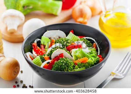 Bowl of healthy vegetarian food. Salad with broccoli, onion, mushroom, carrot and pepper.