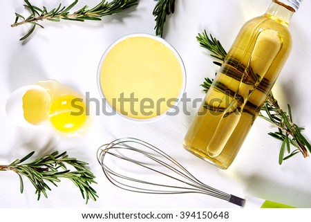bowl of homemade mayonnaise, broken egg, bottle of oil and wire whisk. top view - stock photo
