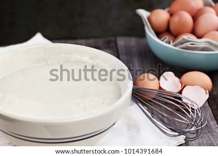 Bowl of homemade pancake batter mix with farm fresh brown eggs in background. Extreme shallow depth of field. Perfect for Shrove Tuesday.