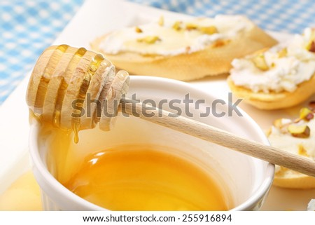 Bowl of honey and bruschetta with goat cheese pistachios and honey  - stock photo