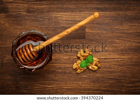 Bowl of honey nuts and mint on wooden table.  Aromatic and tasty. Top view. - stock photo