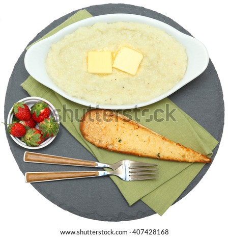 Bowl of Hot Grits with Toast and Strawberries on slate with napkin isolated.