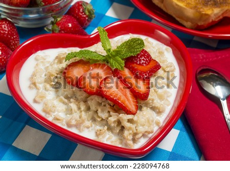 """bowl of hot oatmeal served with fresh strawberries and toast """"oatmeal"""" - stock photo"""