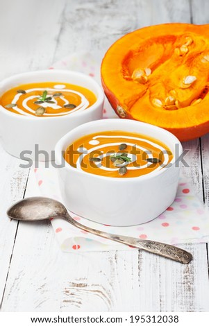 Bowl of hot pumpkin soup with cream on white wooden table - stock photo