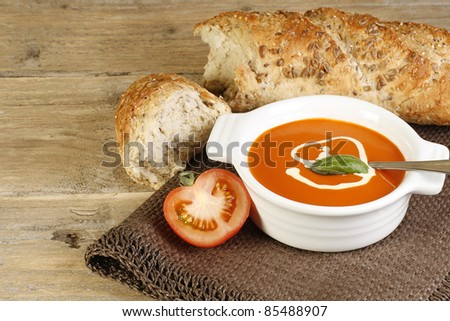 bowl of hot tomato soup and crusty bread on a wooden table - stock photo